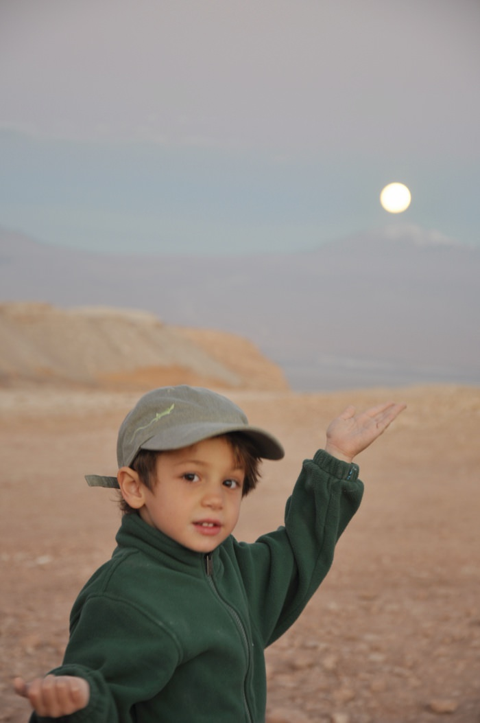 child holding full moon in the Atacama desert, Chile