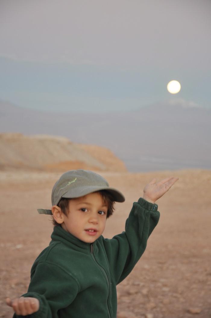 child holding full moon in the Atacama desert, Chile