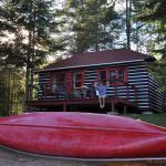 Wooden cottage, red canoe and tall pine trees in the Algonquin Park, Canada