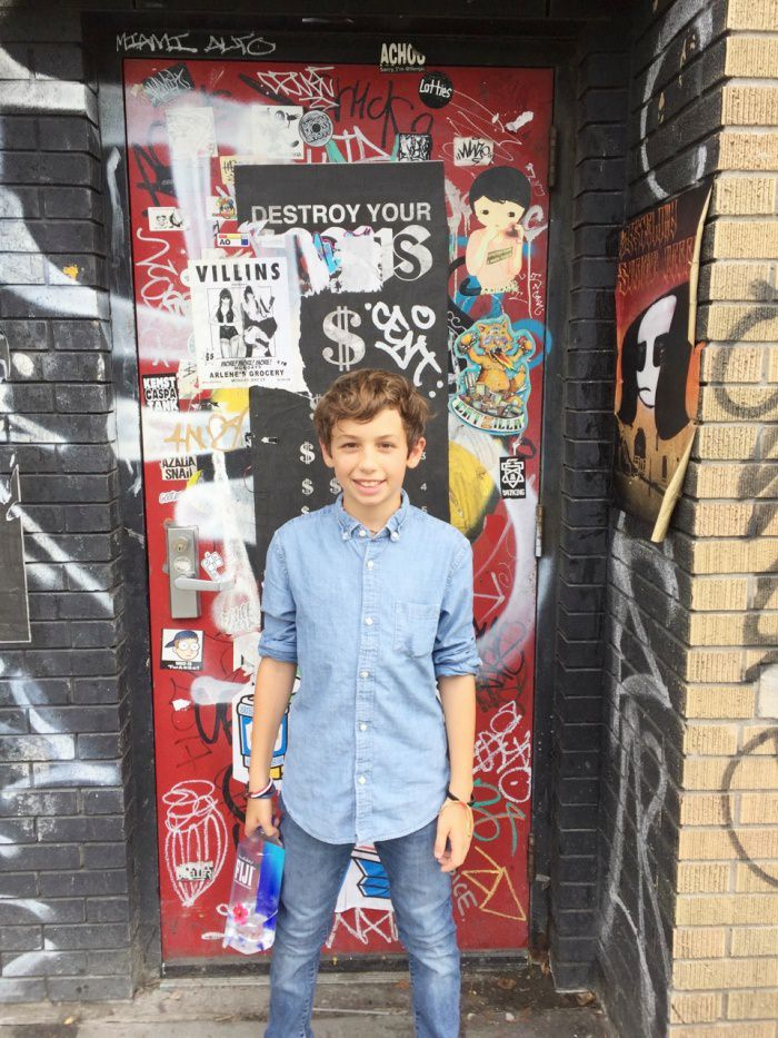 boy posing in front of Brooklyn graffiti